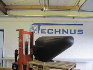 Ein spitzer Schwimmkörper aus der Serie Speedy der auf einer Palette präsentiert wird
