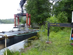Eine Schwimmplattform der Serie Home die mittels eines Kranes in das Wasser gesetzt wird