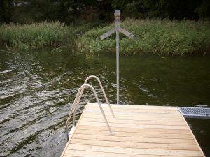 Ein Schwimmsteg mit Holzbelag und montierter Badeleiter