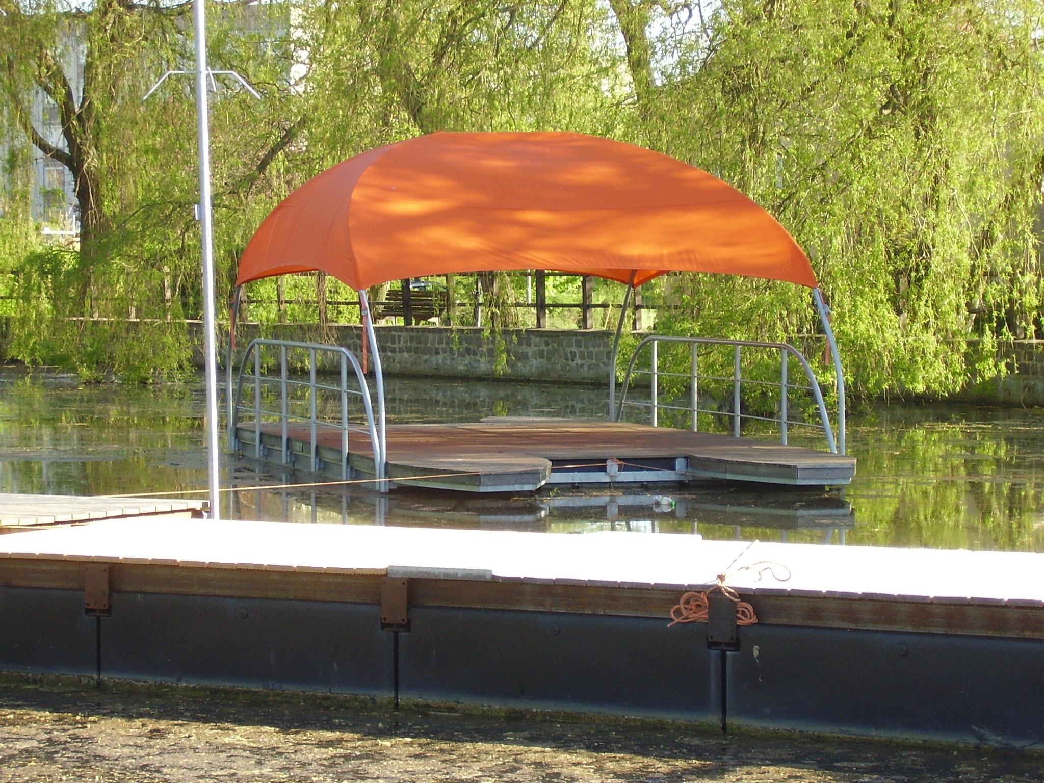 Eine treibende Schwimminsel im Kanal mit großen Sonnenschutz