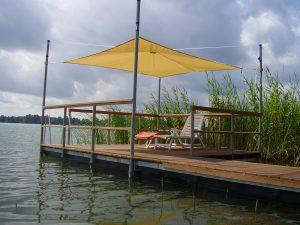 Ein Schwimmsteg mit Liegestuhl und Sonnenschirm