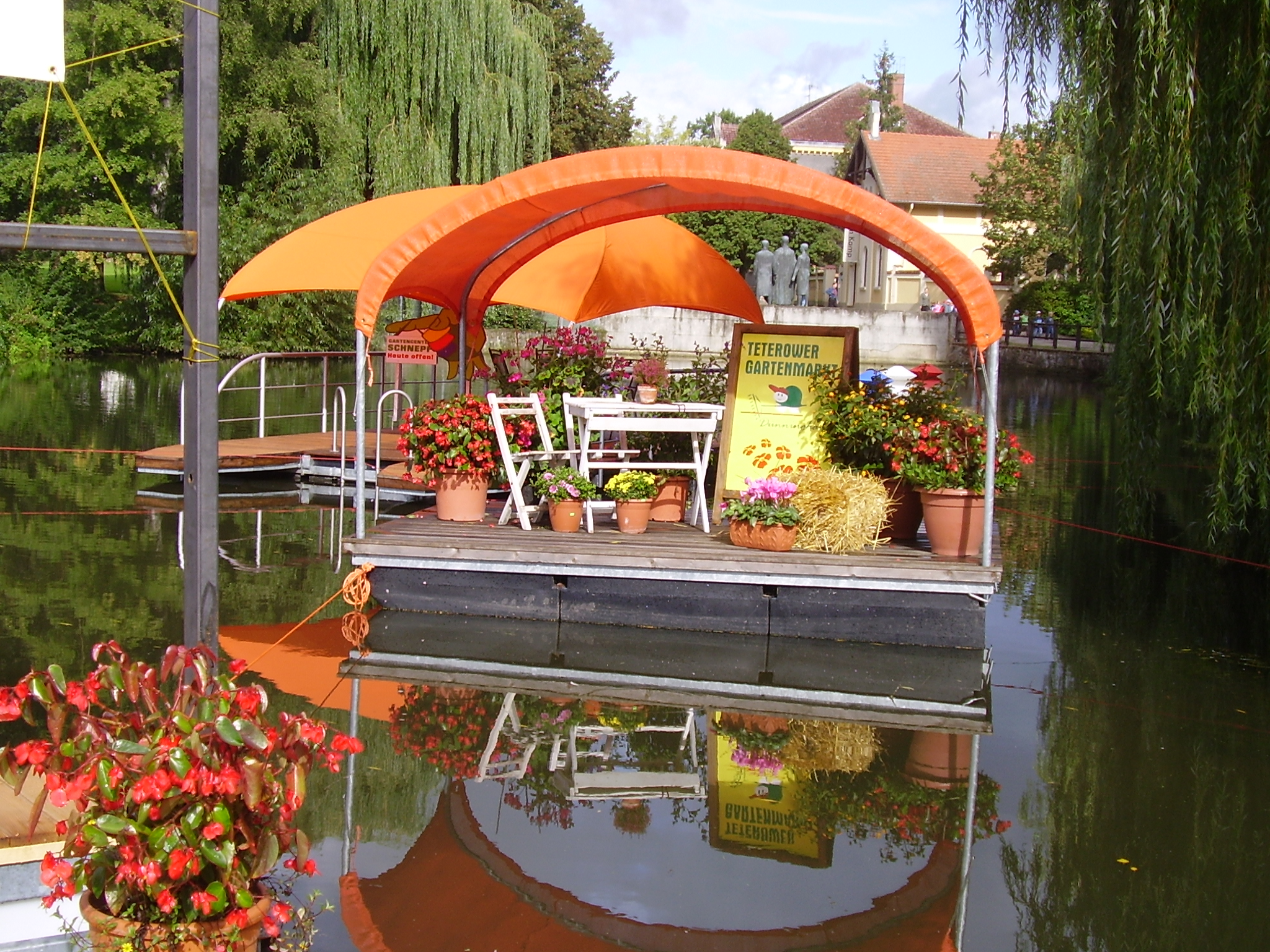 Eine im Wasser treibende Schwimminsel mit Sonnenschutz auf dem Blumen ausgestellt sind